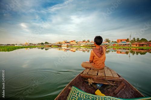 Carta da parati Cambodian boy on prow of small boat overlooking lake