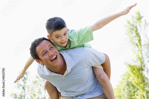Man giving young boy piggyback ride outdoors smiling