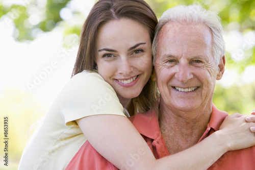 Man and woman outdoors embracing and smiling