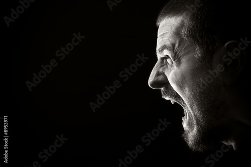 Tableau sur Toile Face of screaming angry man on black background