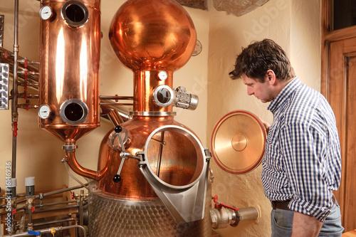 Man in front of distillery - copper Fototapeta