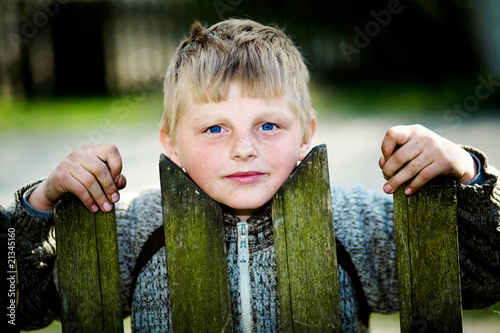 A lad of the village behind the fence Fototapeta