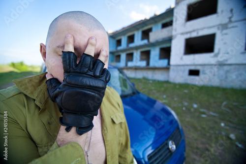 Fototapeta Portrait of a skinhead man near ruined building.