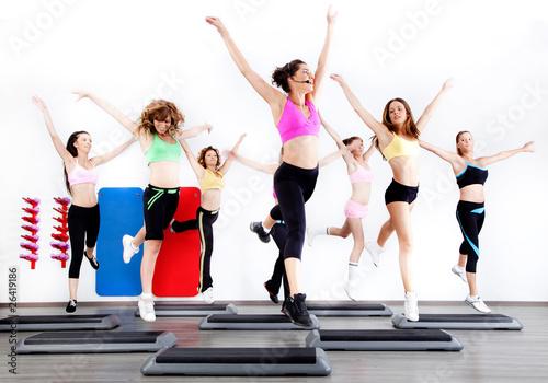 group of women doing aerobics on stepper #26419186