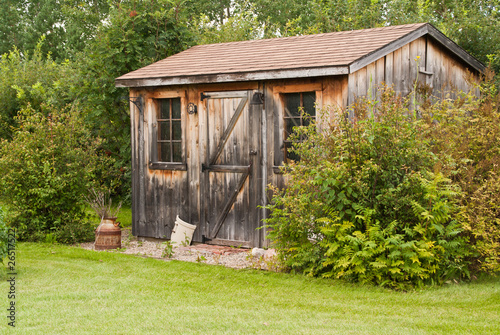 Fotomural A charming, rustic garden shed made from reclaimed timber