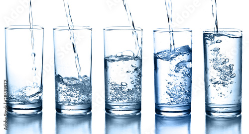 pouring water in a glass collection isolated