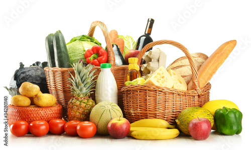 Groceries in wicker basket isolated on white