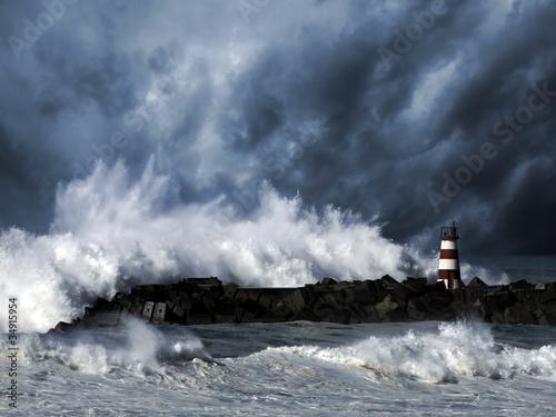 Stormy waves against beacon Fototapeta