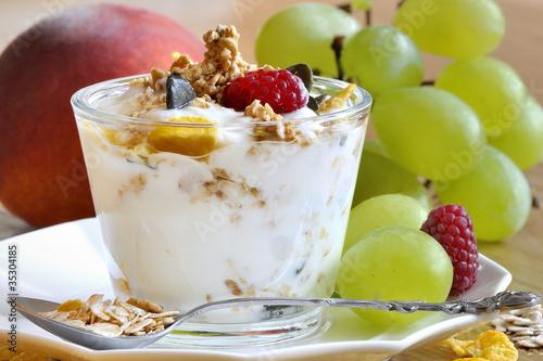 musli z jogurtem w szklanym naczyniu i owoce w tle
