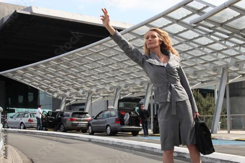 Businesswoman waving taxi Fotobehang