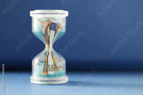 Eurokrise - Durch Sanduhr rinnender Euroschein