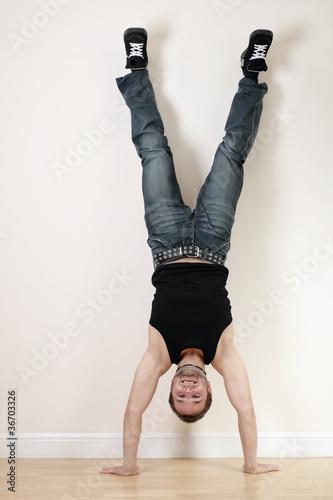 A joyful young man doing a handstand Fototapet