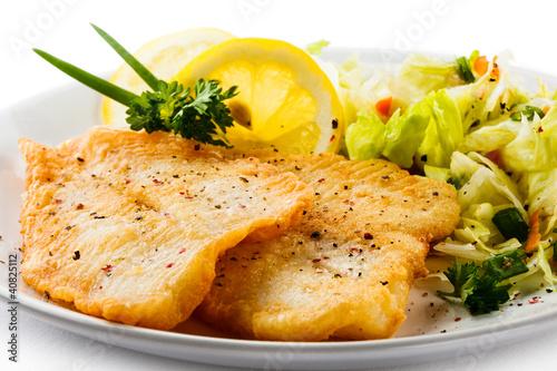 Obraz na plátne Fish dish - fried fish fillets and vegetable salad
