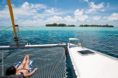 Young woman sunbathing on the catamaran Fotobehang