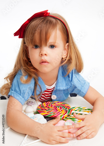 Greedy  girl with pile of sweets Fototapeta