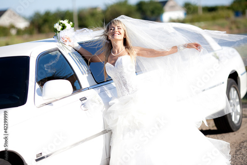 Stampa su Tela young bride standing beside a limousine