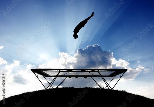 Fototapeta silhouette of gymnast on trampoline in sunset