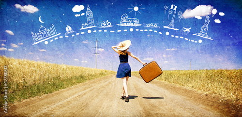 Lonely girl with suitcase at country road dreaming about travel. Fototapet