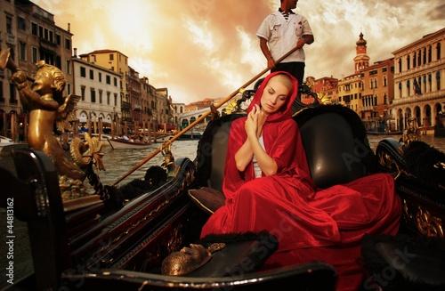 Fotografia Beautiful woman in red cloak riding on gondola