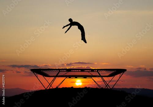 Obraz na plátně gymnast on trampoline in sunset