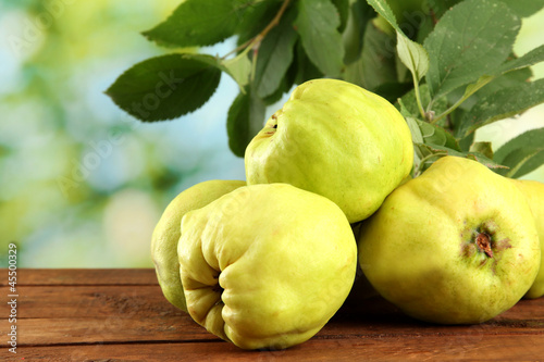 Photographie sweet quinces with leaves, on wooden table, on green background