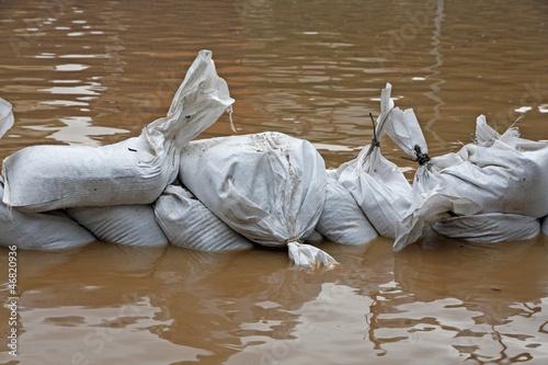 Fotografie, Obraz sandbags for flood defense and brown water