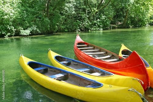 Slika na platnu Four empty plastic canoes in turquoise green river