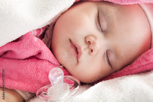 Vászonkép Baby girl sleeps with a pacifier nearby