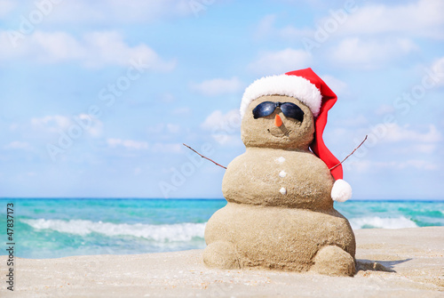 Canvas Print Smiling sandy snowman in red santa hat on the sea beach.