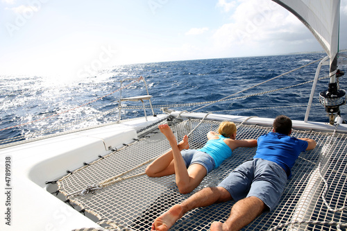 Canvas Couple relaxing on catamaran net looking at the sea