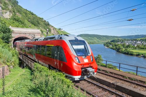 Fototapeta premium Pociąg Intercity opuszczający tunel w pobliżu rzeki Mozeli w Niemczech