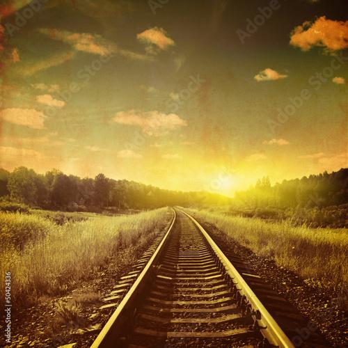 Grunge image of sunset over railroad.
