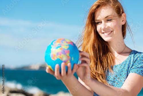 Photo junge frau mit globus am meer