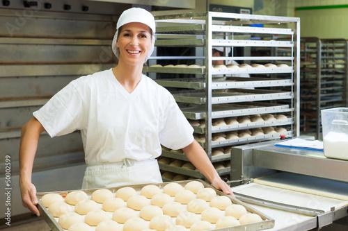 Foto Female baker baking bread rolls