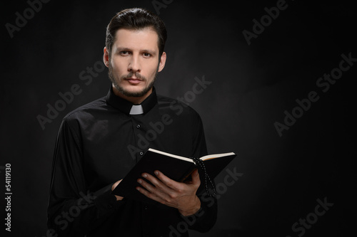 Canvas Print Priest with Holy Bible. Portrait of priest reading the Holy Bibl