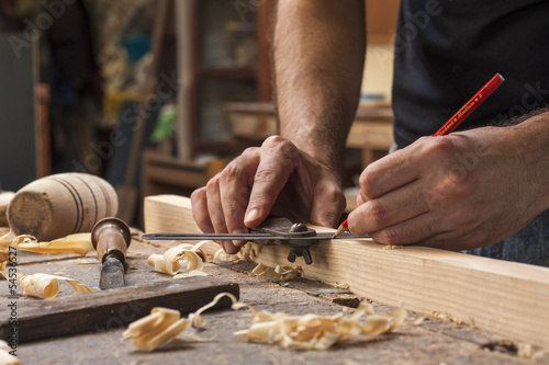 hand of a carpenter taking measurement of a wooden plank Poster Mural XXL