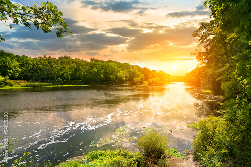 Sunset over the river in the forest