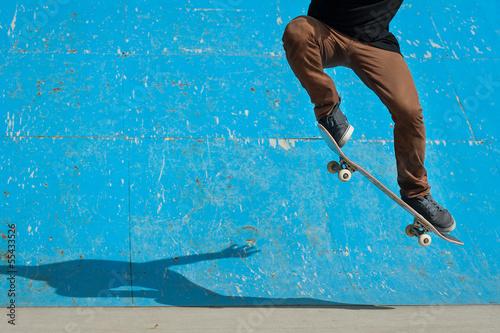 Fotografie, Obraz Skateboarder doing a skateboard trick - ollie - at skate park.