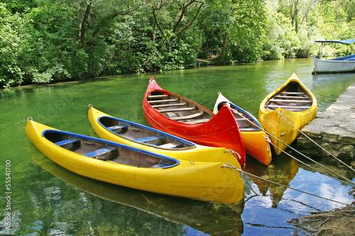 Five empty plastic canoes in turquoise green river Fototapeta
