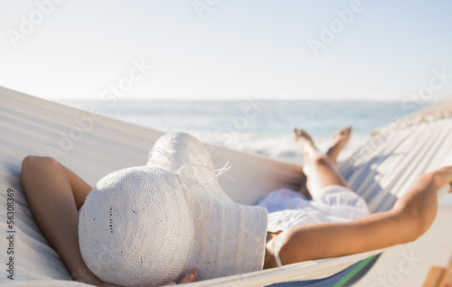 Fotografia Peaceful woman in sunhat relaxing on hammock