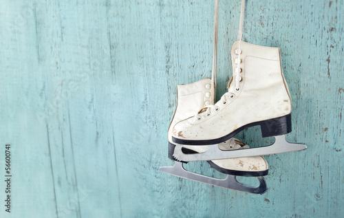 Fototapeta Women's ice skates hanging on blue wooden background