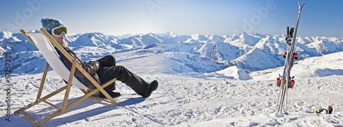 Jeune femme se relaxant dans une chaise sur les pistes de ski, panorama de montagnes enneigées en hiver
