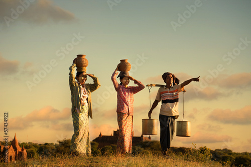 traditional asian farmer during sunset at a rice field in bagan, Fotobehang