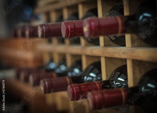 Fotografie, Obraz Červené víno lahví naskládané na dřevěné regály