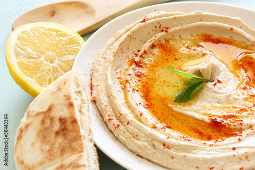 hummus dip plate and lemon on wooden table