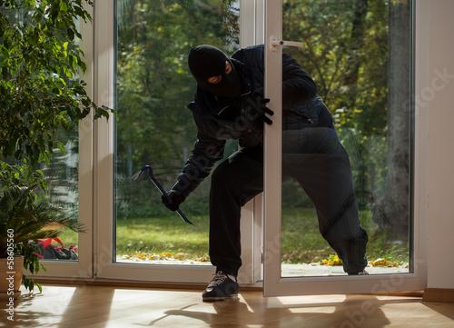Canvas Print Burglar entering through the balcony window
