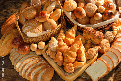 Variety of bread in wicker basket on old wooden background.