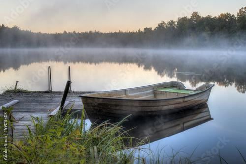 Fototapeta A dirty boat by a wooden pier