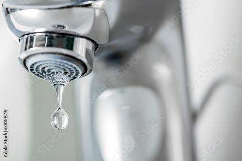 Fototapeta Tap closeup with dreaping waterdrop. Water leaking, economy conc