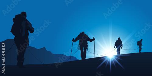 Cordée d'alpinistes marchant ensemble pour atteindre le sommet d'une montagne Fototapeta